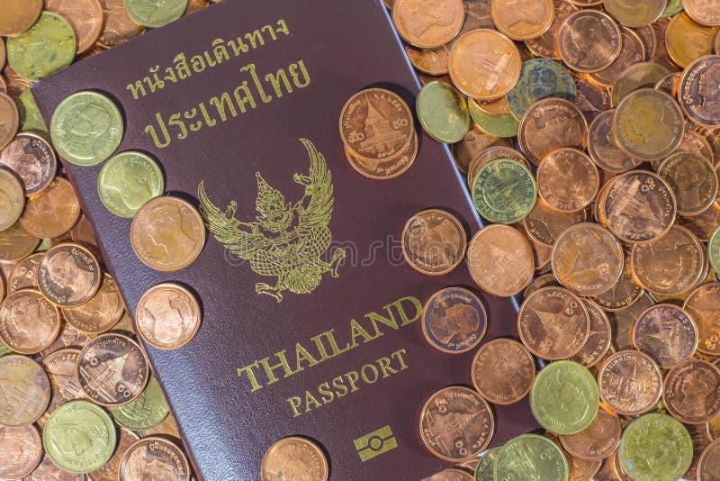 Passaporto tailandese su un mucchio delle monete fotografia stock