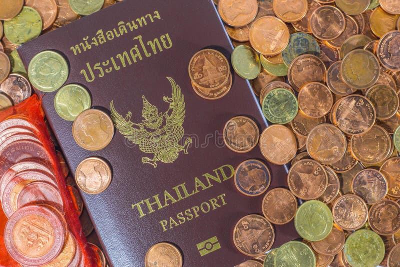 Passaporto tailandese su un mucchio delle monete fotografia stock libera da diritti