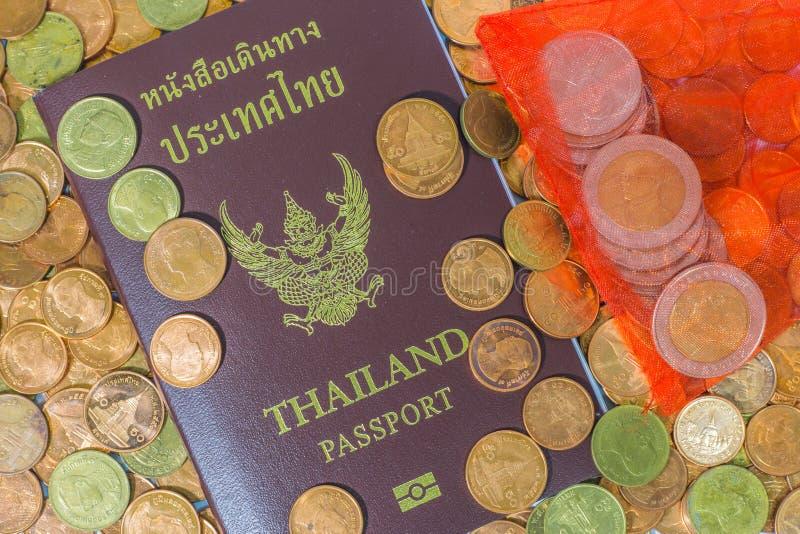 Passaporto tailandese su un mucchio delle monete immagine stock