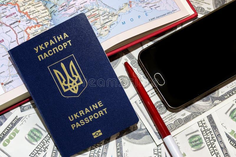Passaporto ucraino sui precedenti delle fatture del cento-dollaro con un telefono e una carta fotografia stock libera da diritti