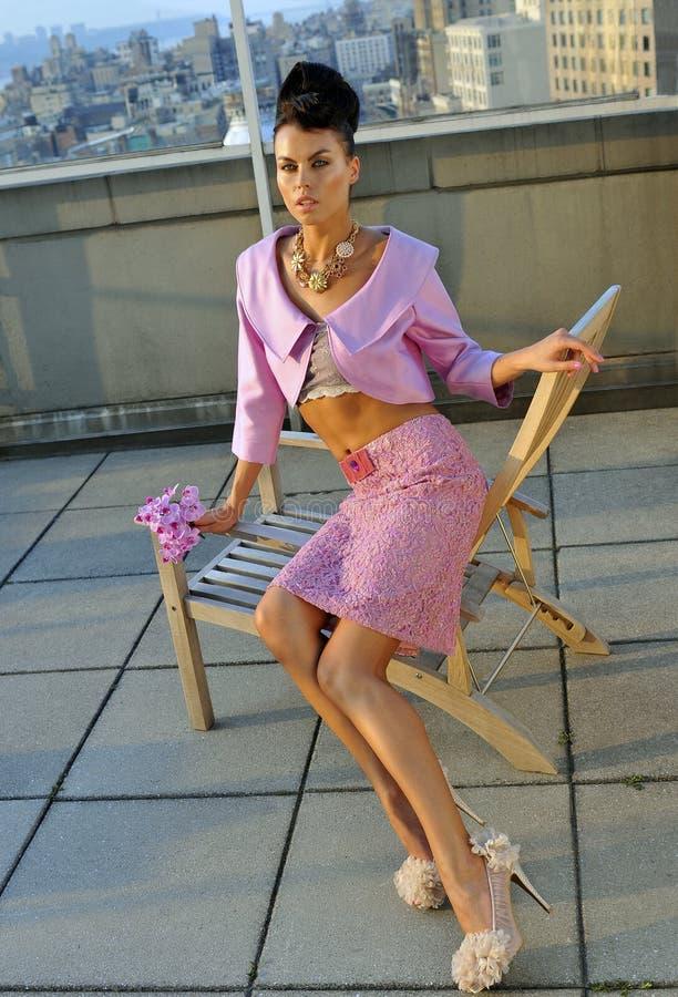 Passar bärande sömnadrosa färger för modell att posera på taket royaltyfri bild