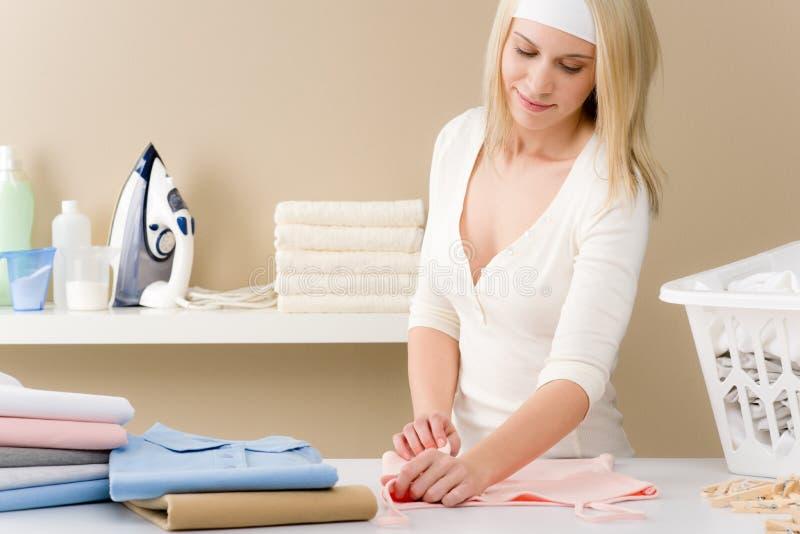 Passar da lavanderia - roupa de dobramento da mulher fotos de stock royalty free