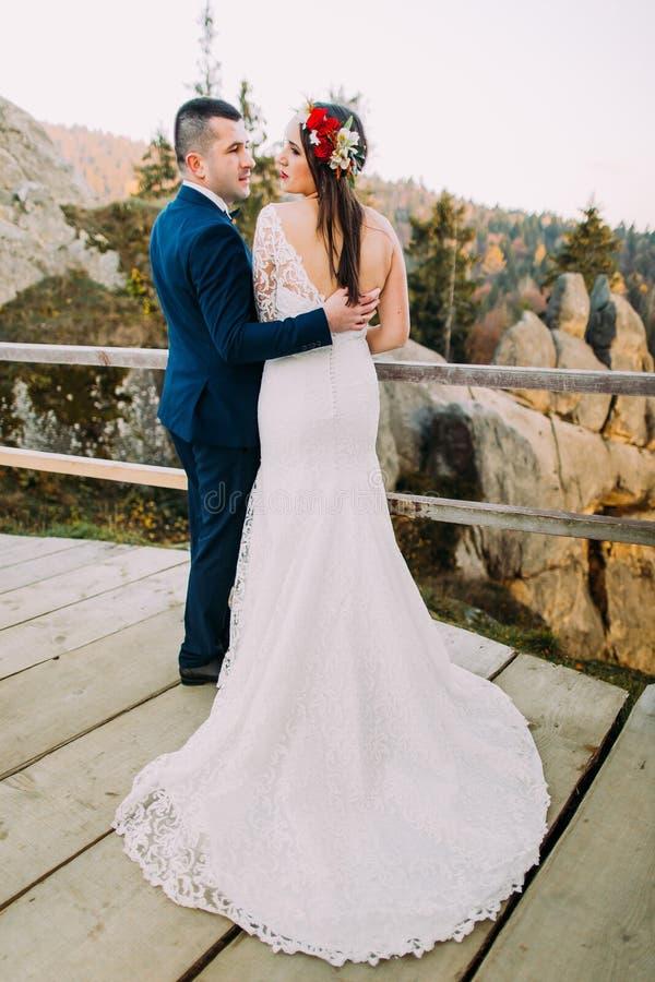 Passar stilfulla blått för elegant brudgum rymma lovingly hans charmiga brud i ursnyggt långt vitt klänninganseende på trä arkivbild