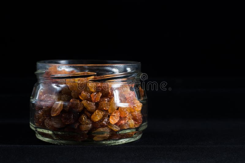 Passas em um frasco de vidro selado para o armazenamento em um fundo preto, isolado imagem de stock