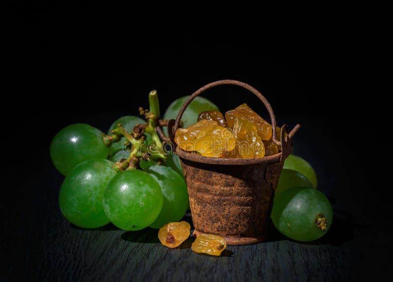 Passas em uma cubeta pequena, uvas em um fundo escuro imagem de stock royalty free