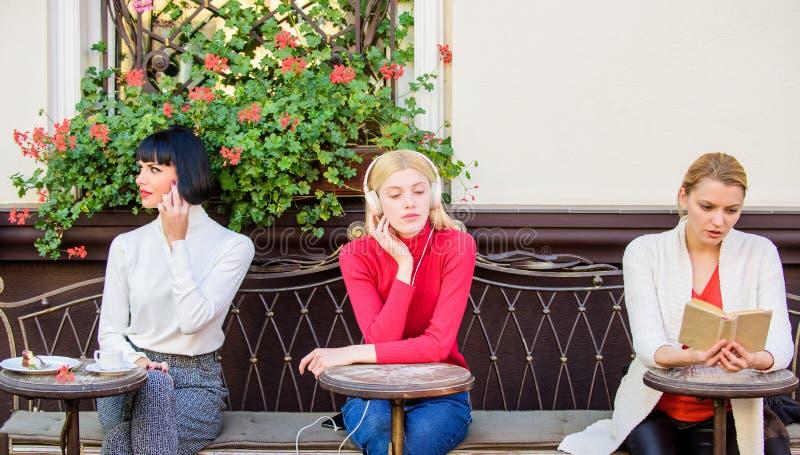 Passatempo e lazer Interesses diferentes O terraço bonito do café das mulheres do grupo mante-se distraído com discurso de leitur fotografia de stock royalty free