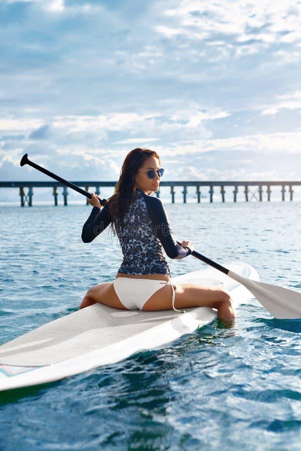 passatempo Menina que rema na prancha Mulher nova na praia do console de Formentera imagens de stock royalty free