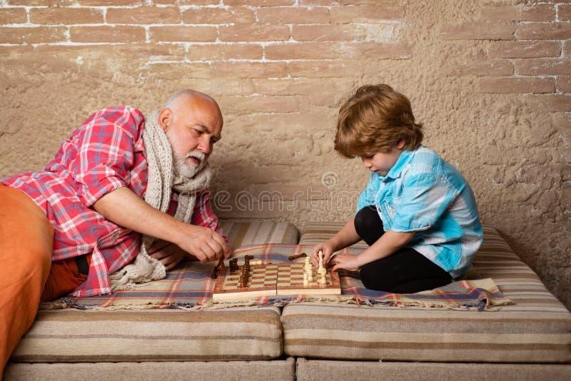 Passatempos da xadrez - avô com neto em uma xadrez de jogo gera??es Mi?do que joga a xadrez Xadrez de jogo de primeira geração fotos de stock royalty free