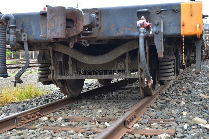 Passe as rodas e os choques da mola do trem de mercadorias do trilho imagem de stock