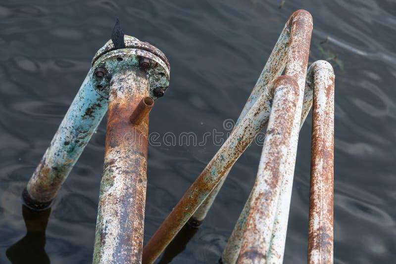 Passe as tubulações oxidadas que entram nas profundidades do lago foto de stock