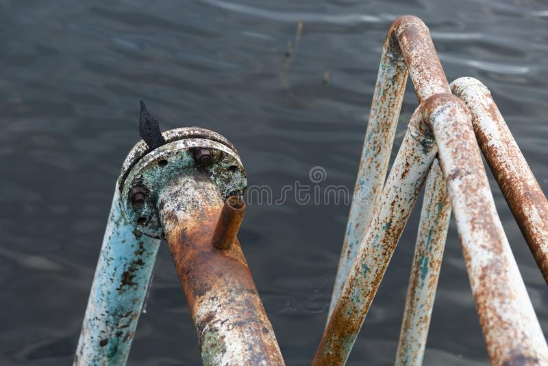 Passe as tubulações oxidadas que entram nas profundidades do lago imagem de stock royalty free