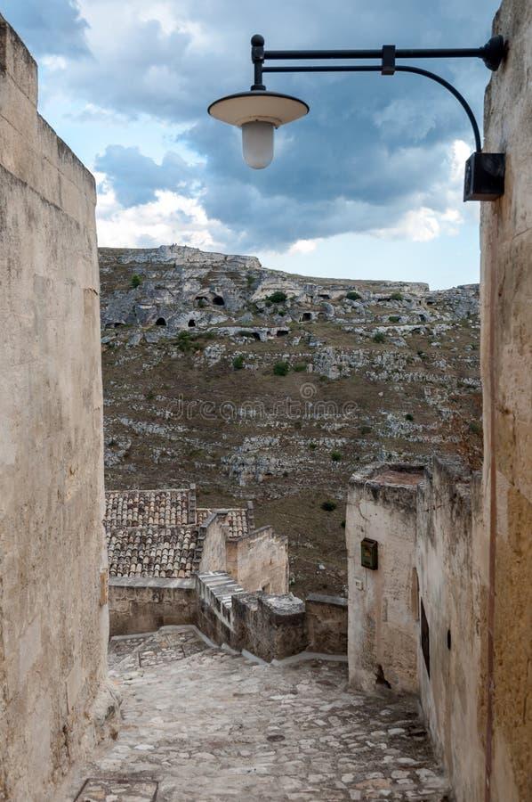 Passe com a lanterna que conduz à vista de cavernas antigas de Sassi foto de stock