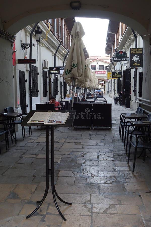 Passe com os cafés exteriores no centro velho de Bucareste fotografia de stock
