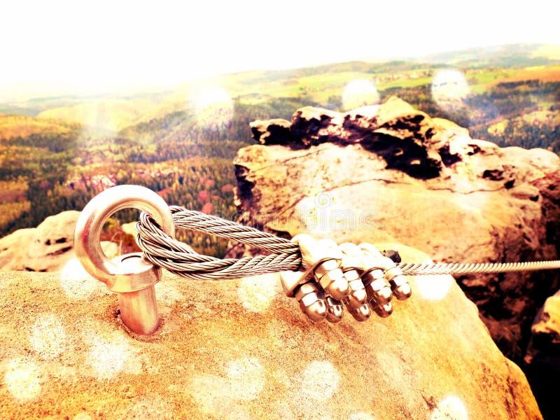 Passe a corda torcida esticada entre rochas no remendo dos montanhistas através do ferrata A corda fixada no bloco pelos parafuso imagem de stock