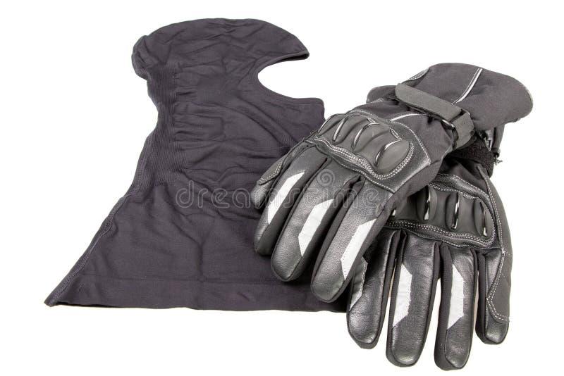 Passe-montagne de moto avec les gants noirs dans la table blanche image stock