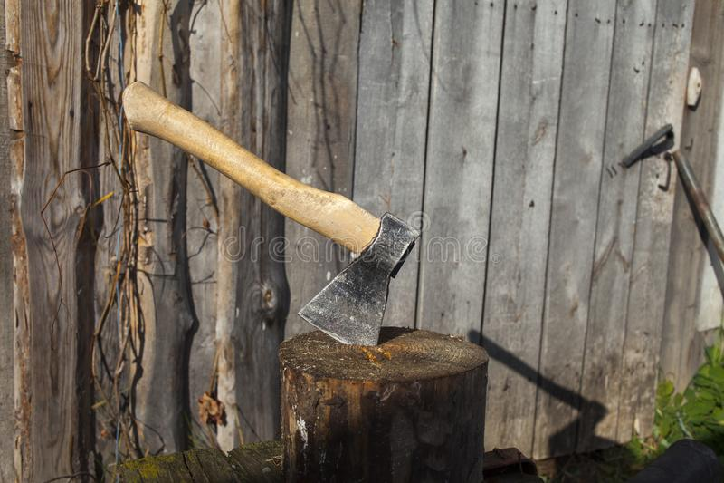 Passe o machado com um punho de madeira em uma plataforma da árvore fotos de stock