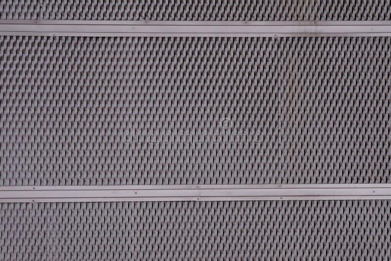 Passe o revestimento da placa da folha de metal com furos perfurados em um teste padrão geométrico e em um efeito da oxidação imagens de stock