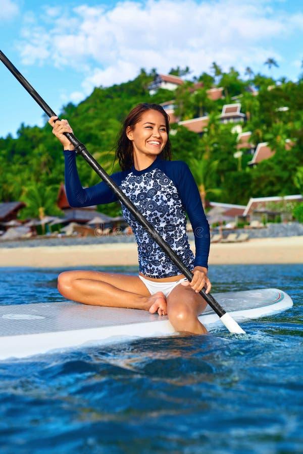 passe-temps Fille barbotant sur la planche de surf Course d'été W récréationnel images stock