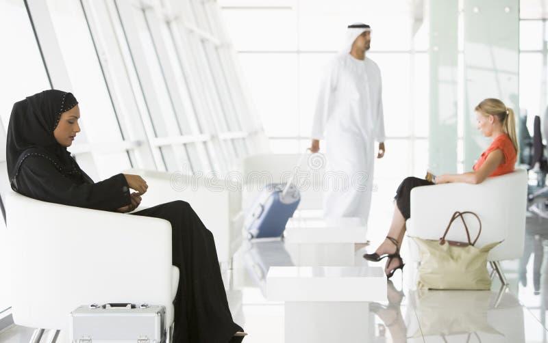 Passeggeri che attendono nel salotto di partenza dell'aeroporto fotografia stock libera da diritti
