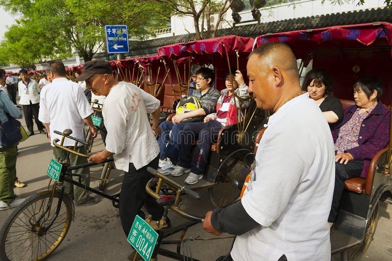 Passeggeri di trasporto dei risciò alla via di Futong accanto al lago Houhai a Pechino, Cina immagine stock