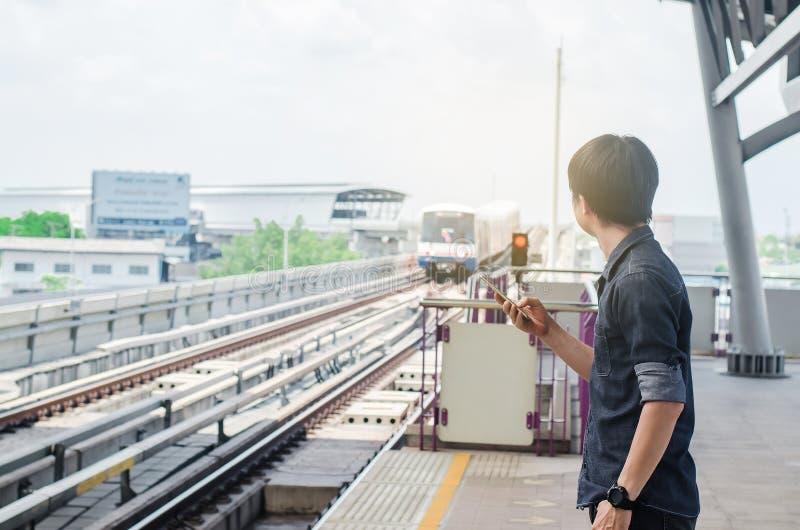 Passeggero asiatico dell'uomo che per mezzo dello smartphone e guardando BTS nella stazione ferroviaria, attesa dello skytrain su fotografie stock