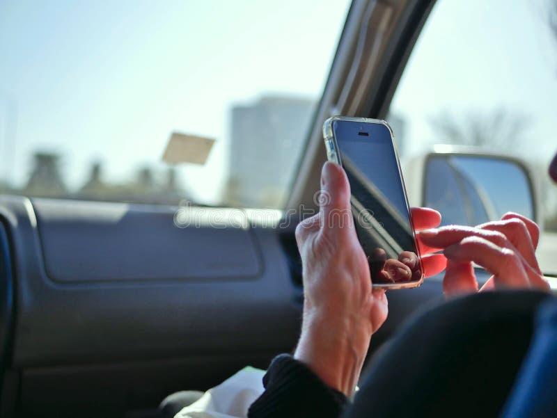 Passeggero in automobile che esamina Smart Phone sulla strada per la navigazione mentre guidando fotografia stock