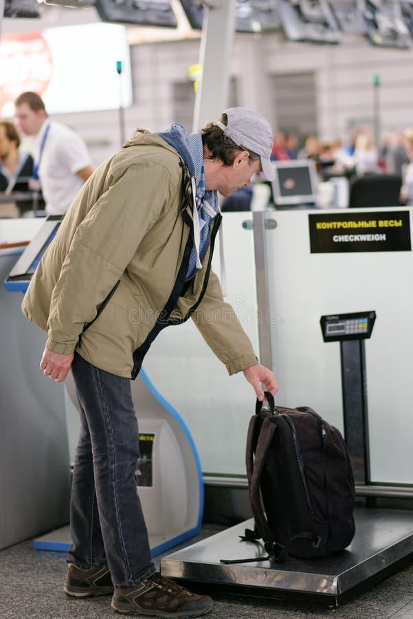 Passeggero che controlla il peso dei suoi bagagli immagine stock libera da diritti