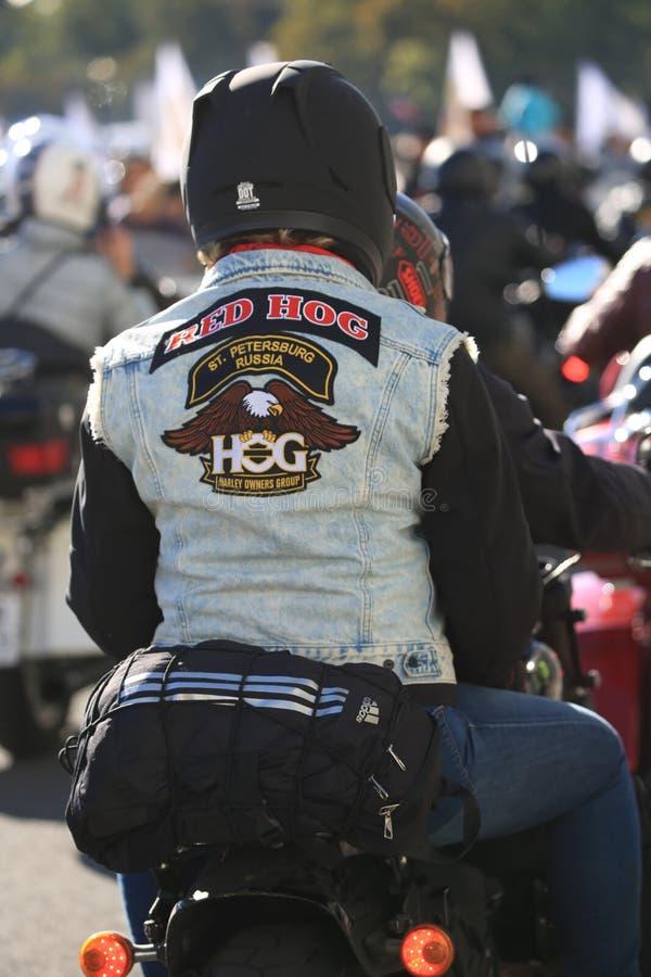 Passeggero del motociclo in una maglia del denim con i simboli del GRUPPO dei PROPRIETARI di HARLEY russo fotografie stock libere da diritti