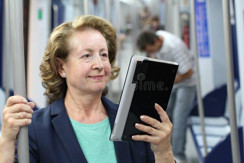 Passeggero felice che usando WiFi mentre viaggiando dentro un treno fotografie stock