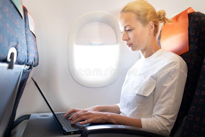 Passeggero femminile caucasico attraente che lavora al computer portatile moderno facendo uso del collegamento senza fili a bordo fotografia stock libera da diritti