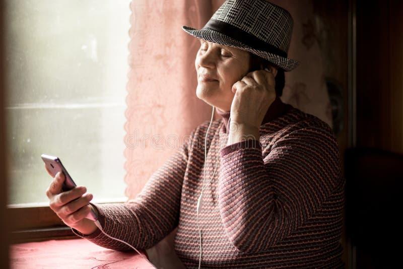 Passeggero senior felice della donna che ascolta la musica in treno e che guarda attraverso la finestra fotografia stock libera da diritti