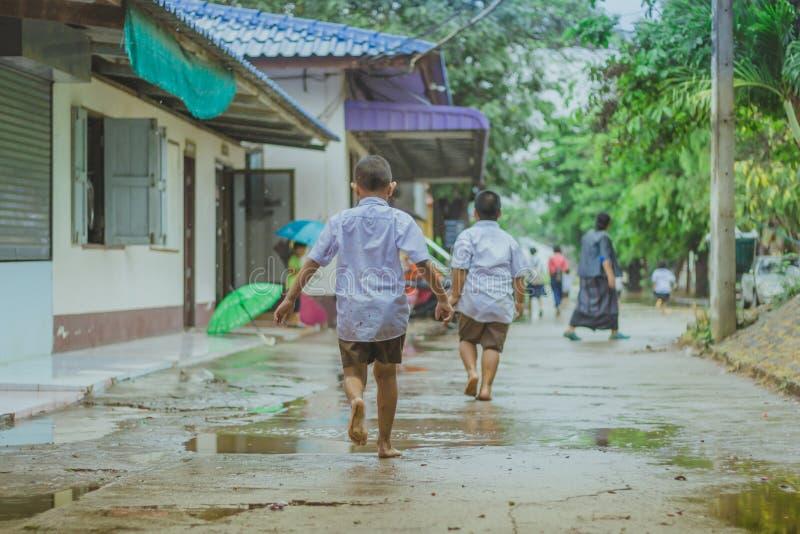 Passeggiata degli studenti all'inondazione dopo pioggia fotografia stock libera da diritti