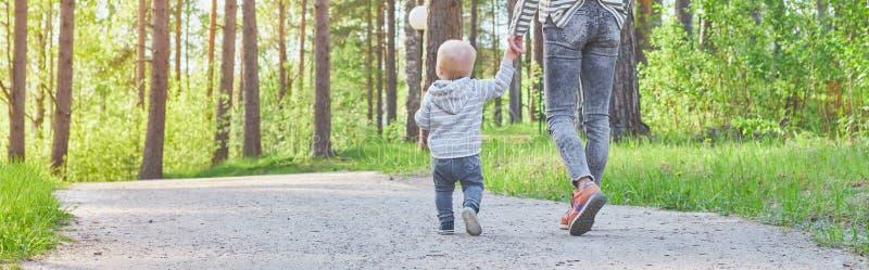 Passeggiata del bambino e della madre dalla maniglia nel parco in tempo soleggiato di estate Vista posteriore immagini stock