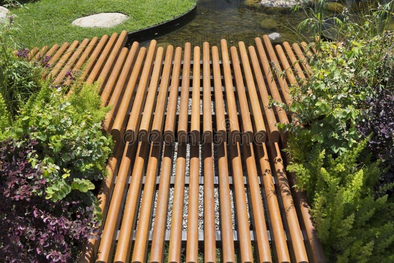 Passeggiata del bordo di legno nel patio del giardino lungo il lato con uno stagno immagine stock libera da diritti