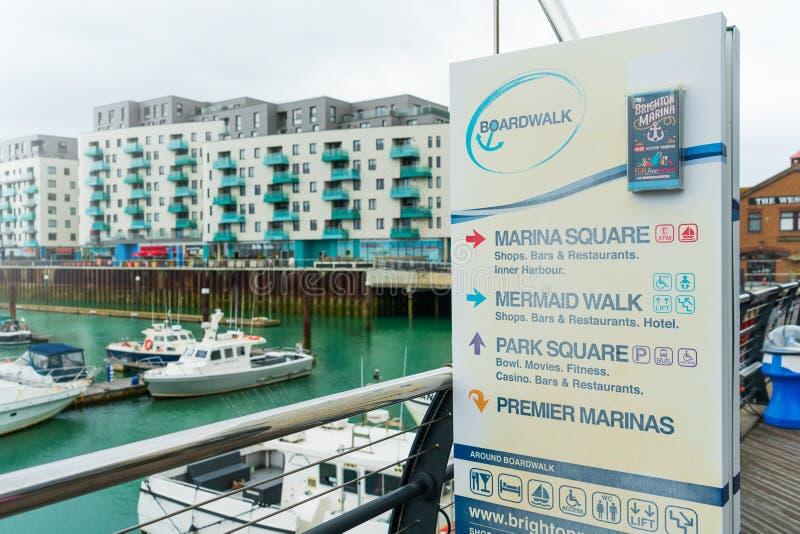 Passeggiata del bordo del porticciolo con il segnale di informazione che mostra le direzioni Marina Bay con la vendita delle barc immagini stock libere da diritti