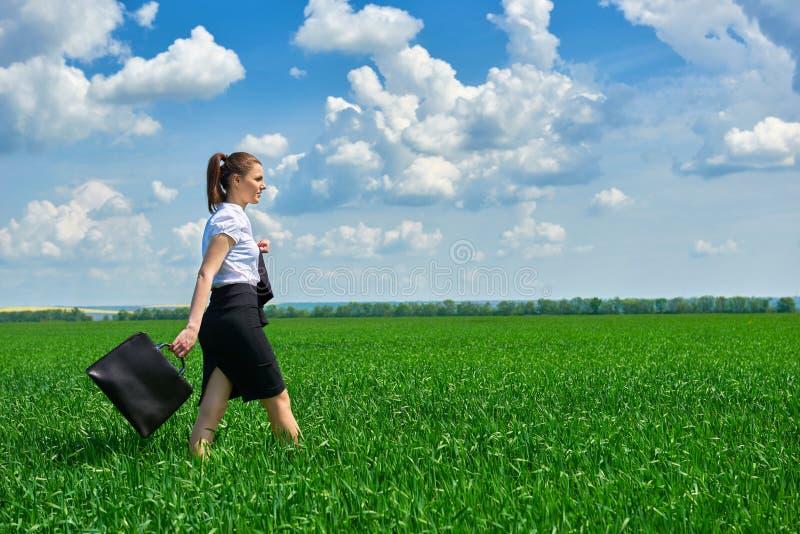 Passeggiata della donna di affari sul campo di erba verde all'aperto La bella ragazza si è vestita in vestito, il paesaggio della immagine stock