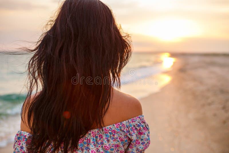 Passeggiata della giovane donna su una spiaggia selvaggia vuota verso i fasci luminosi celesti che cadono dal cielo, fotografia stock
