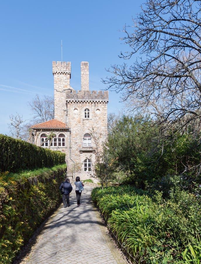 Passeggiata di due persone lungo il percorso lungo il vicolo verde sui precedenti di un castello antico immagini stock