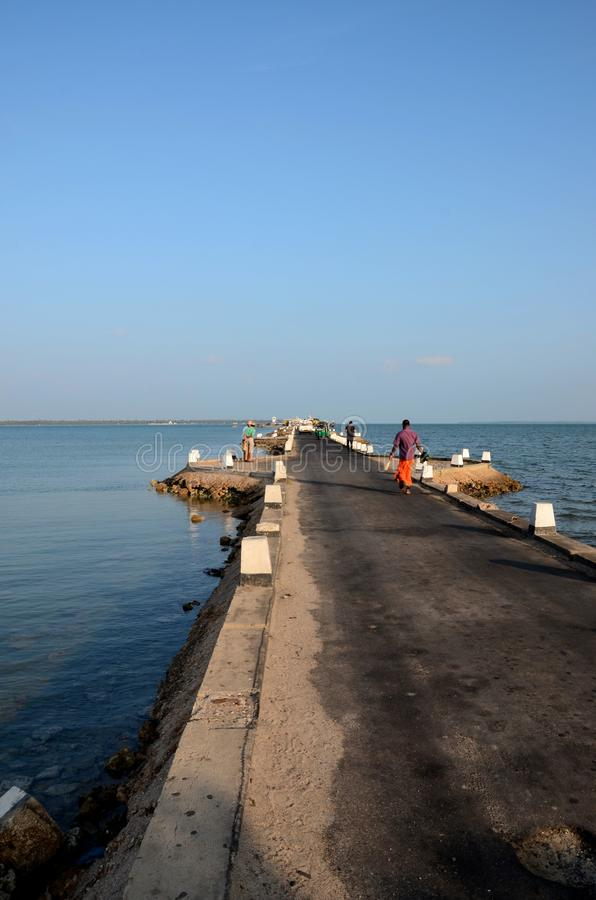Passeggiata di Sri Lankans su una strada della strada soprelevata fuori verso un molo in acqua Jaffna Sri Lanka fotografie stock libere da diritti
