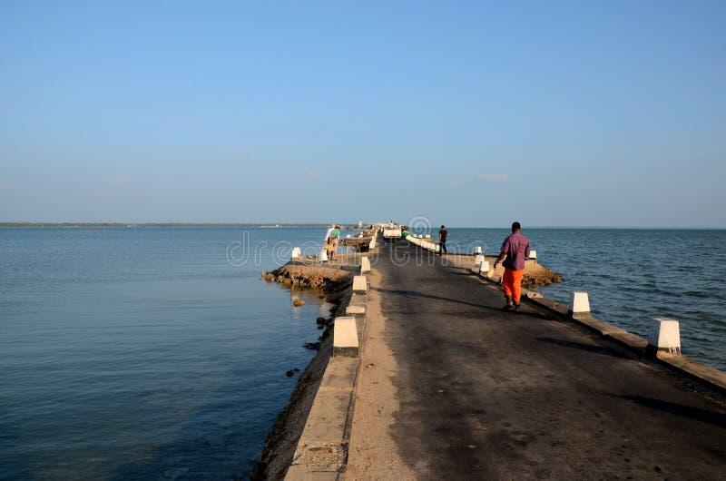 Passeggiata di Sri Lankans su una strada della strada soprelevata fuori verso un molo in acqua Jaffna Sri Lanka immagine stock