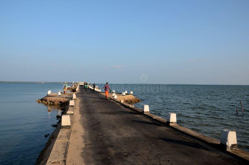 Passeggiata di Sri Lankans su una strada della strada soprelevata fuori verso un molo in acqua Jaffna Sri Lanka immagini stock
