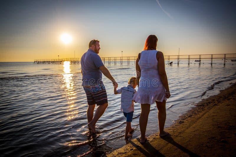 Passeggiata felice della famiglia sulla spiaggia fotografia stock
