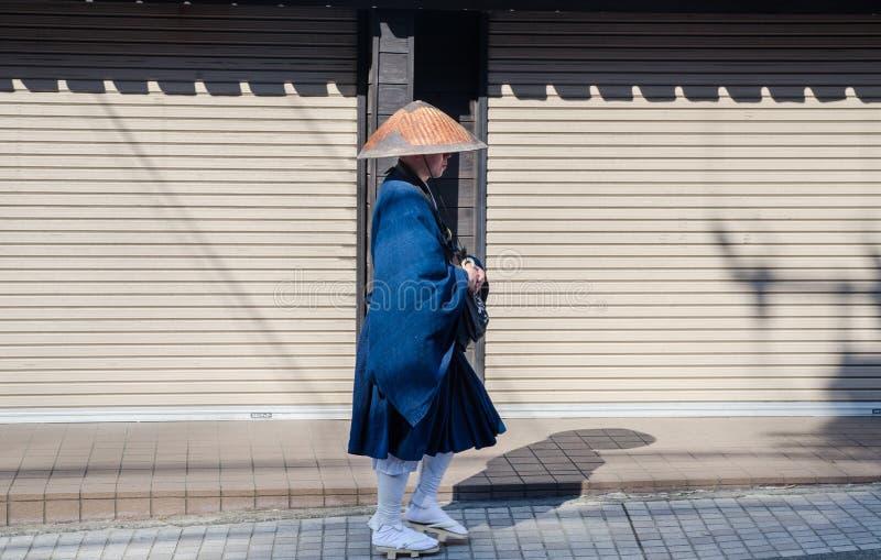 Passeggiata giapponese indefinita del monaco sulla via della città di Kamakura fotografie stock libere da diritti