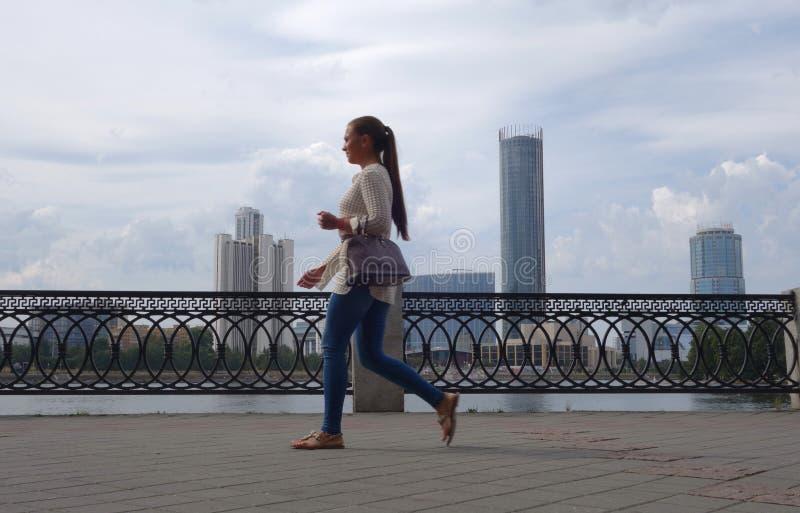 Passeggiata lungo l'argine contro lo sfondo dei grattacieli fotografie stock