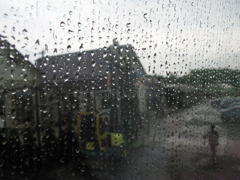 Passeggiata nella pioggia della persona vicino al caff? del bordo della strada vago fotografia stock