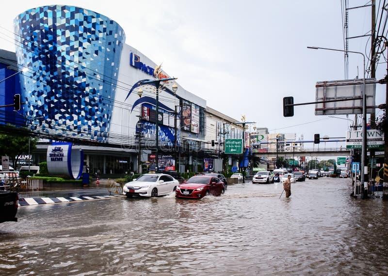 Passeggiata non identificata dell'uomo attraverso l'inondazione dopo pioggia alla città di Sriracha immagini stock libere da diritti