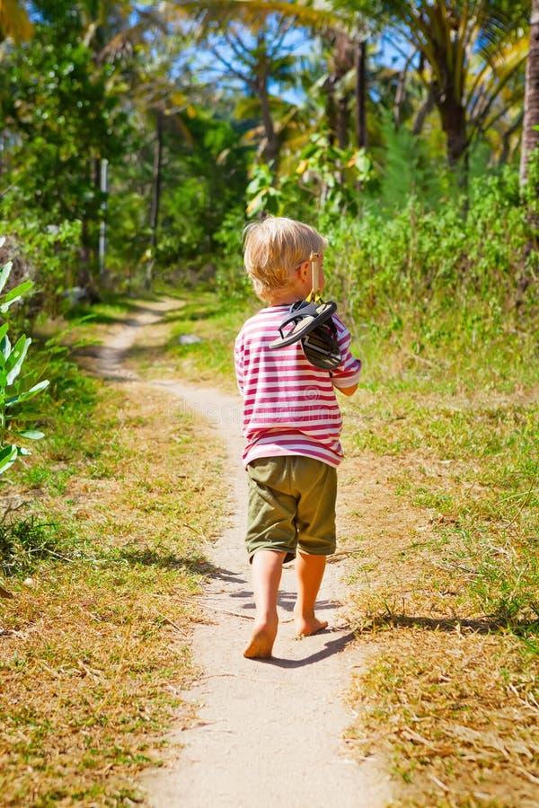 Passeggiata scalza felice del bambino da solo sulla spiaggia dal percorso della giungla fotografie stock