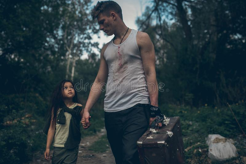 Passeggiata senza tetto della figlia e del padre attraverso la discarica immagini stock libere da diritti
