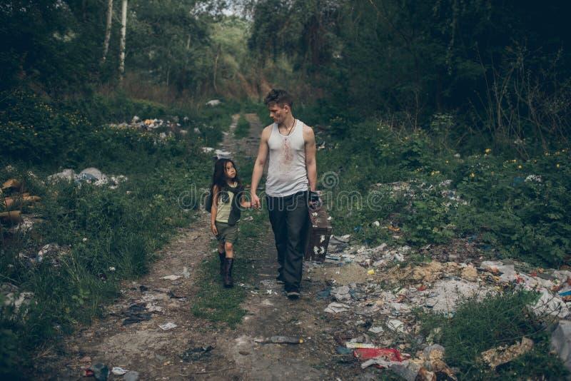 Passeggiata senza tetto della figlia e del padre attraverso la discarica fotografia stock