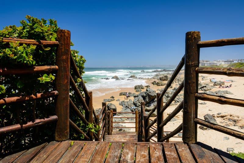 Passeio à beira mar de madeira que conduz à praia em Keurboomstrand, África do Sul imagens de stock royalty free